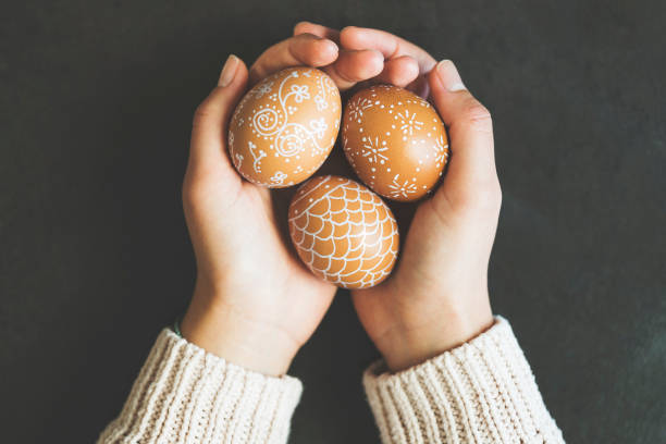 Hands holding handpainted easter eggs stock photo