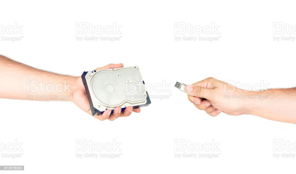 Hands Holding Hard Drive Versus Small Flash Memory Stick stock photo