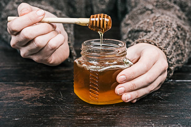 hands holding honey - miel photos et images de collection