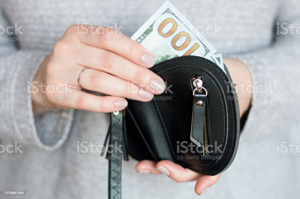 hands holding hundred dollar and wallet