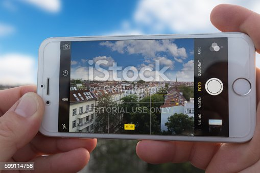 istock Hands holding Iphone 6, taking picture of city skyline 599114758