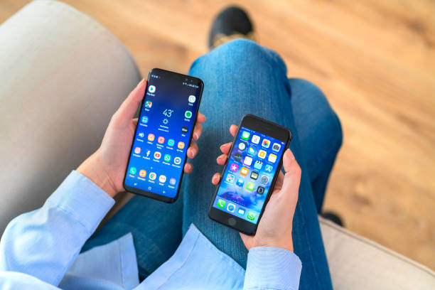 Hands holding iPhone and Samsung Galaxy stock photo