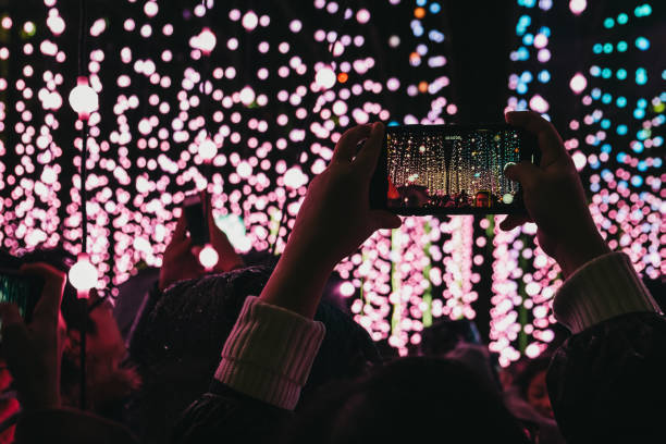 Hands holding iPhone mobile phone taking photos of installation at Winter Lights, London, UK. London, UK - January 26, 2019: Human hands holding iPhone mobile phone above head, taking photos of light installation at Winter Lights, yearly lights and installations festival in Canary Wharf. taken on mobile device stock pictures, royalty-free photos & images