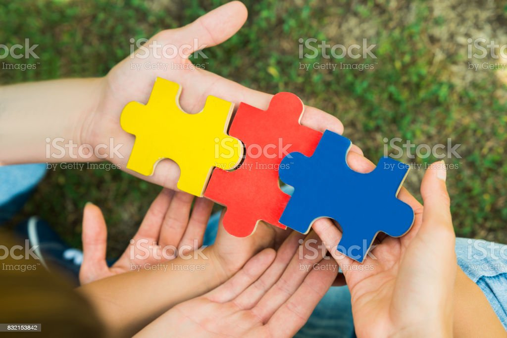 Hands Holding Jigsaw Puzzle Pieces stock photo