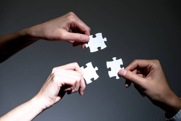 hands holding jigsaw puzzles, business to business, business matching concept - three people stock photos and pictures
