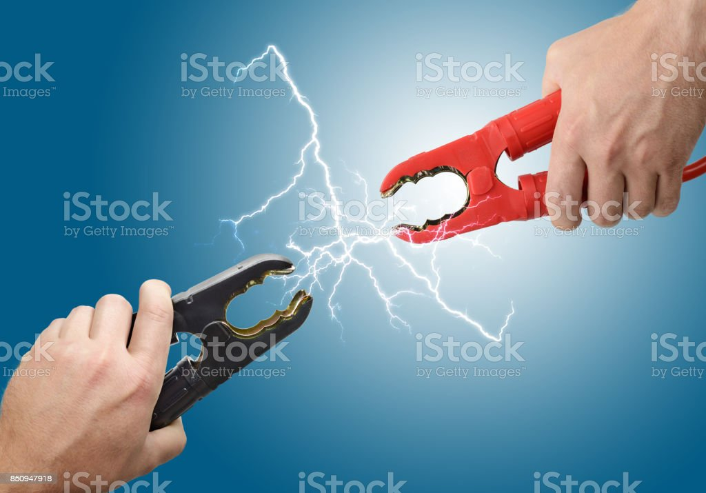 Hands holding jump start connectors stock photo