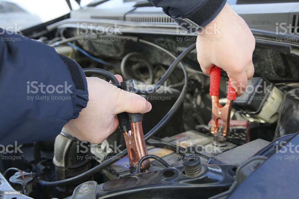 Hands holding jumper leads on car engine stock photo