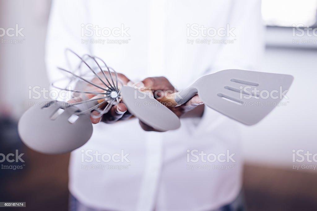 Hands holding kitchen utensils stock photo