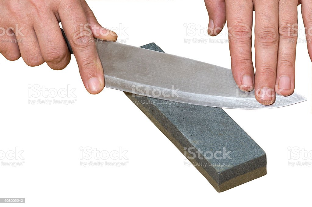 Hands holding knife and whetstone isolated on white background stock photo