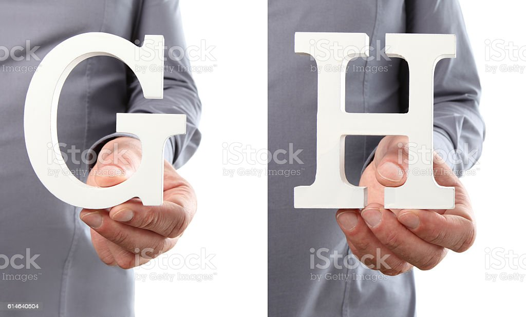 Hands holding letter G and H from alphabet isolated stock photo