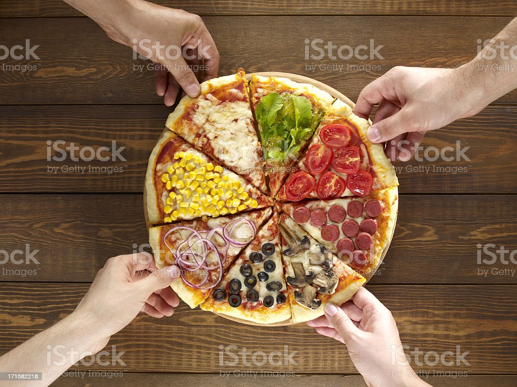 Hands Holding Mixed Pizza Slices stock photo