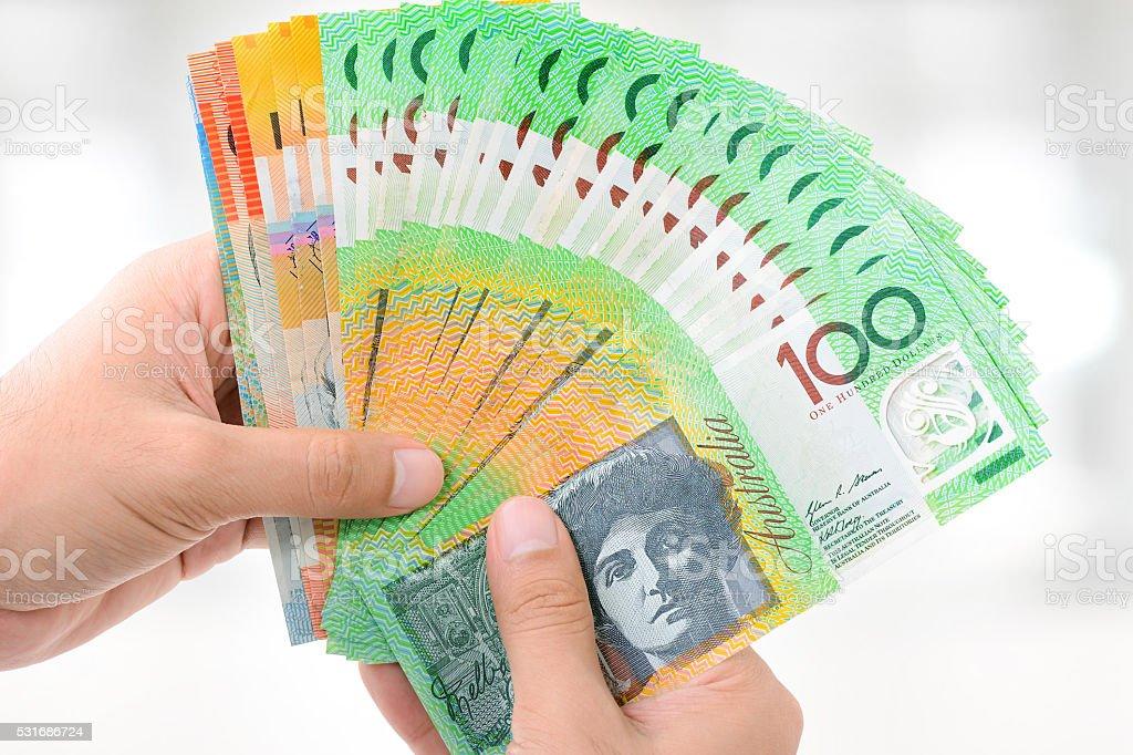 Hands holding money, Australian dollar (AUD) banknotes stock photo