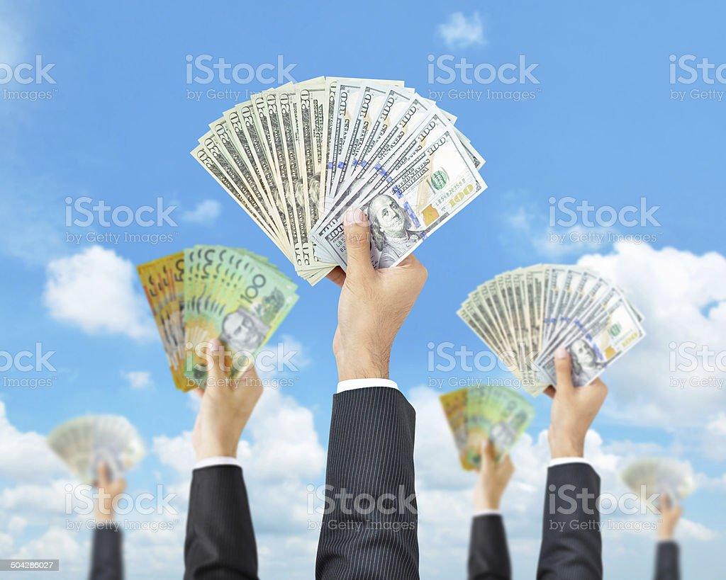 Hands holding money (multi currencies) - money raising, funding concept stock photo