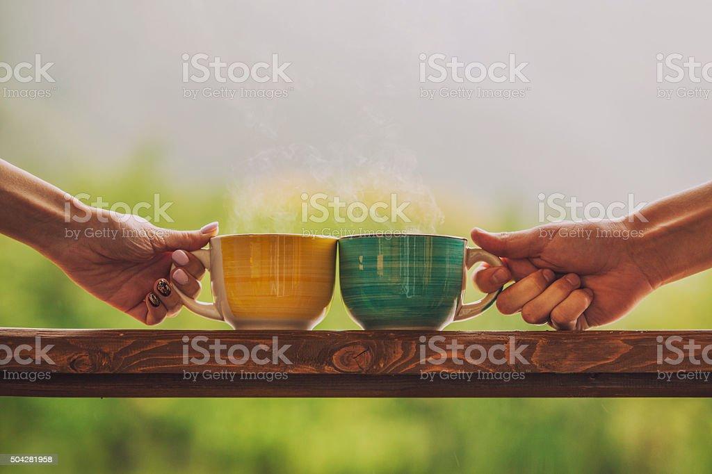 Mains tenant la tasse de boisson chaude, avec thé - Photo