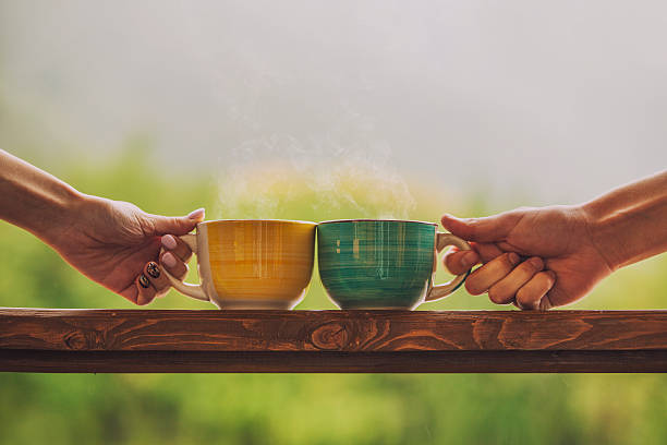 hands holding mug with hot beverage, with tea - couple lap stock photos and pictures