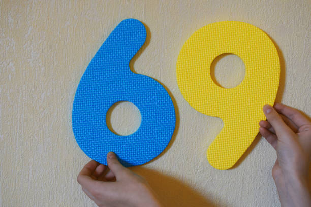 hands holding number sixty nine - number 69 stock photos and pictures