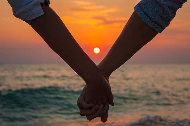 paar hände halten am meer bei sonnenuntergang - twilight teile stock-fotos und bilder