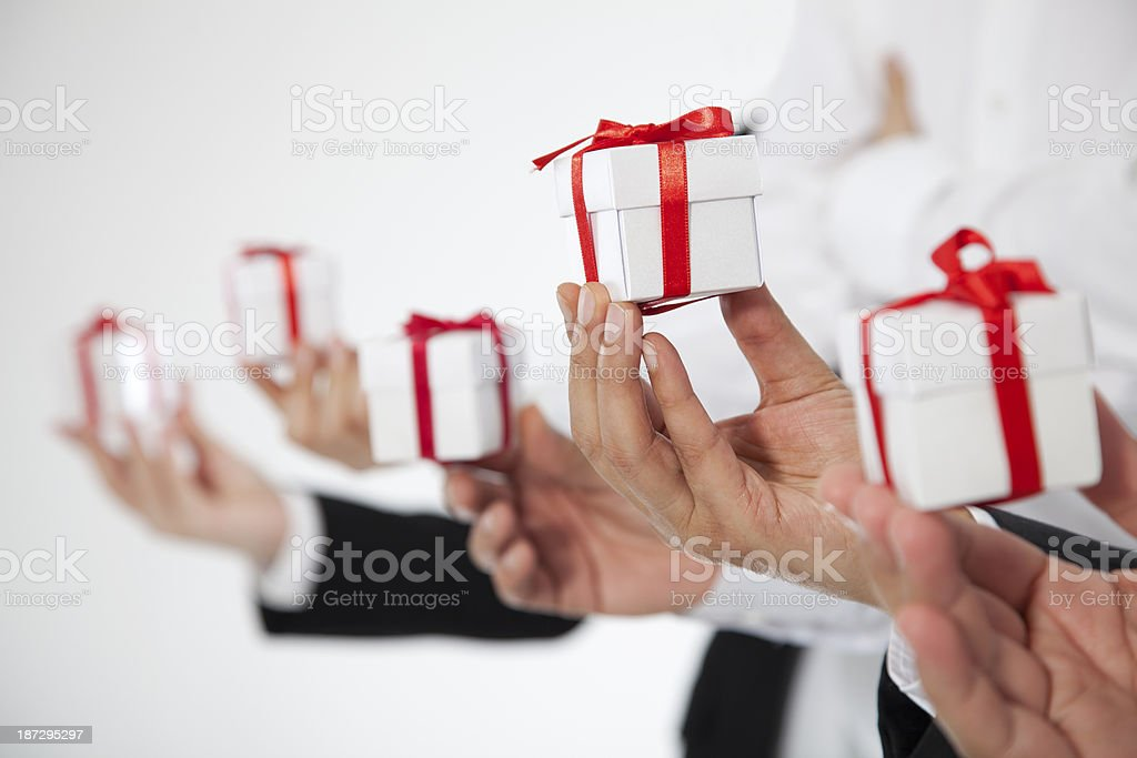 Hands holding out white gifts wrapped in red ribbon royalty-free stock photo