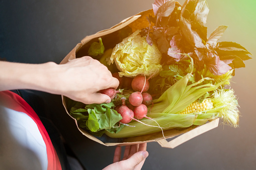 istock hands holding package with healthy raw fresh food on dark wooden surface 1031719270
