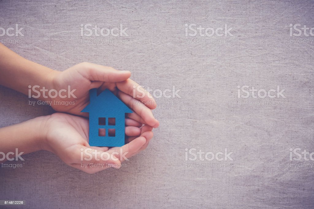 hands holding paper house, homeless shelter and real estate concept stock photo