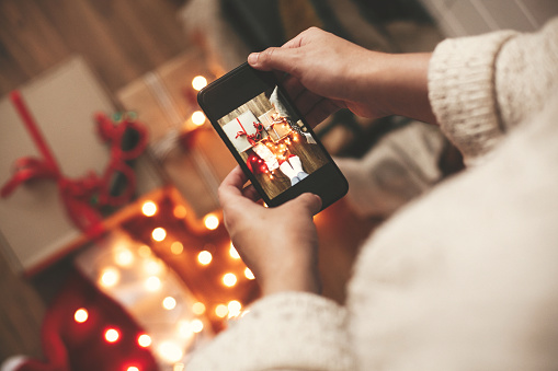 Hands holding phone and taking photo of christmas gift boxes, santa hat, lights on wooden background in dark room. Stylish hipster girl in sweater making christmas instagram flat lay photo
