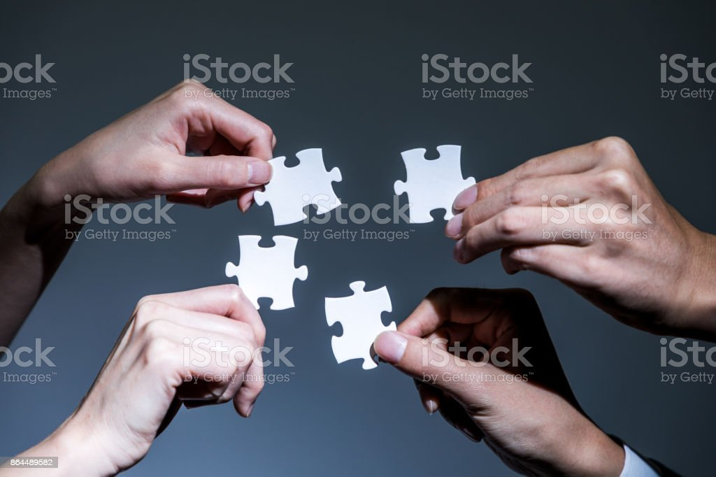 hands holding pieces of jigsaw puzzle, business to business, business matching concept stock photo