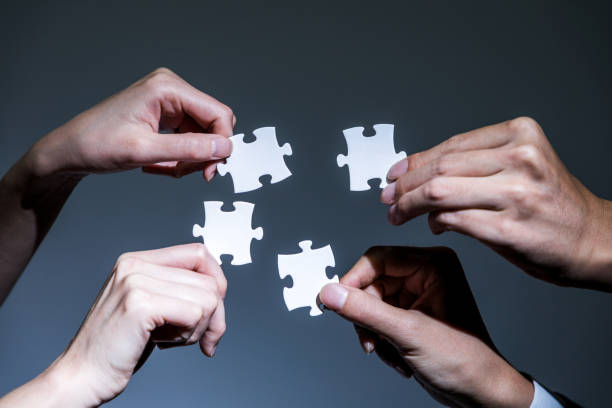 hands holding pieces of jigsaw puzzle, business to business, business matching concept - four people stock photos and pictures