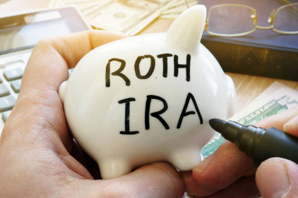 Hands holding piggy bank with Roth IRA. Pension plan. stock photo