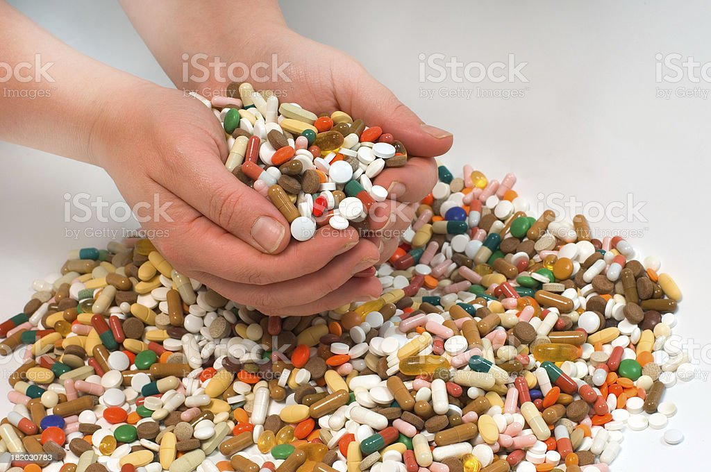 hands holding pills stock photo