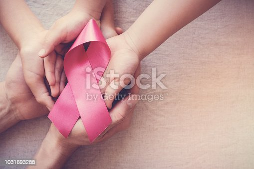 istock hands holding pink ribbon, breast cancer awareness, October pink concept 1031693288