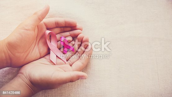istock Hands holding Pink Ribbons toning background, Breast cancer awareness and Abdominal cancer awareness 841425486