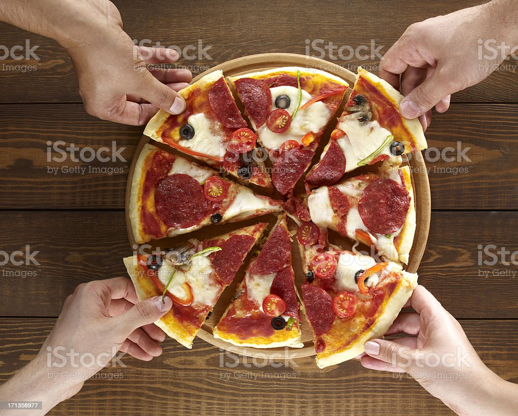 Hands Holding Pizza Slices stock photo