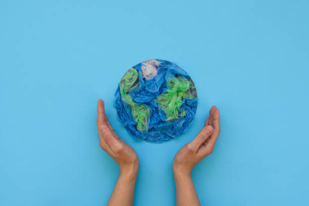 hands holding planet earth made from plastic disposable packages on blue background. save the world, creative, environment pollution or world earth day concept. top view - sostenibilità foto e immagini stock