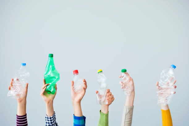 manos sosteniendo la botella de plástico - plástico fotografías e imágenes de stock