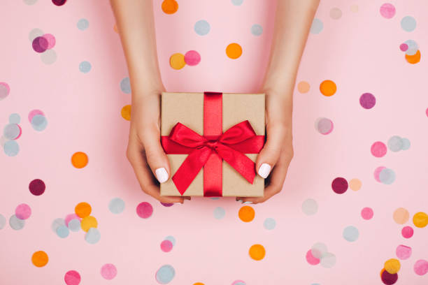Hands holding present box Woman hands holding present box with red bow on pastel pink background with multicolored confetti. Flat lay style. gift box stock pictures, royalty-free photos & images