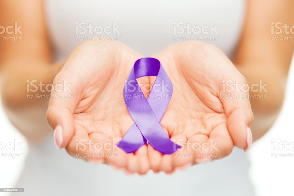 hands holding purple awareness ribbon stock photo