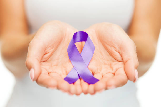 hands holding purple awareness ribbon - domestic violence stock pictures, royalty-free photos & images