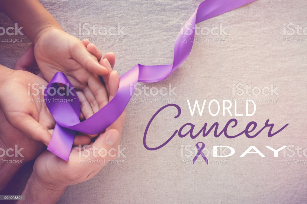 Hands holding Purple ribbons, World Cancer Day stock photo