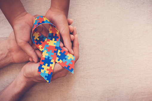 istock Hands holding puzzle ribbon for autism awareness 1134365962