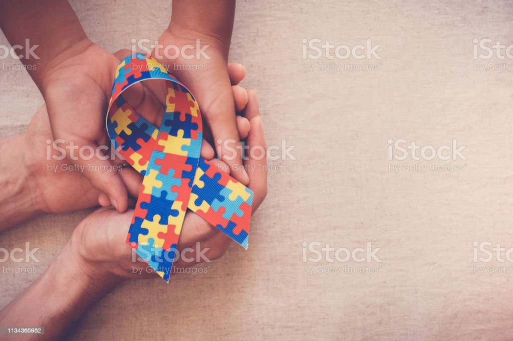 Hands holding puzzle ribbon for autism awareness stock photo