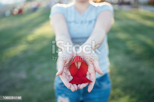 istock Hands holding red AIDS awareness ribbon 1065054166