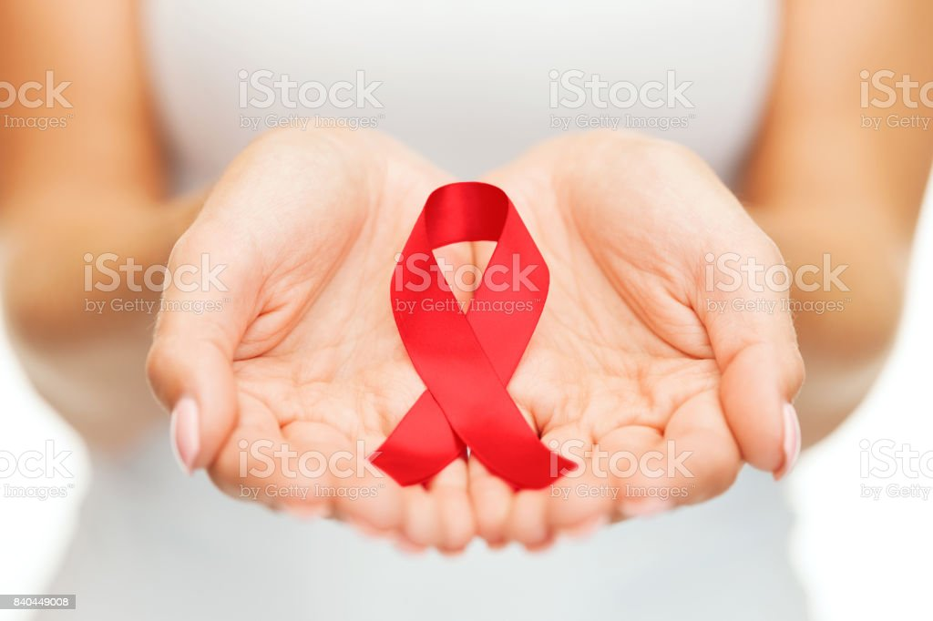 hands holding red AIDS awareness ribbon stock photo
