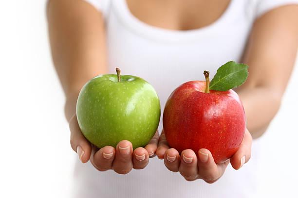 Mãos segurando a maçã vermelha e verde - foto de acervo