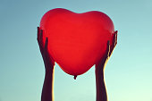 Hands holding red balloon in the shape of heart.