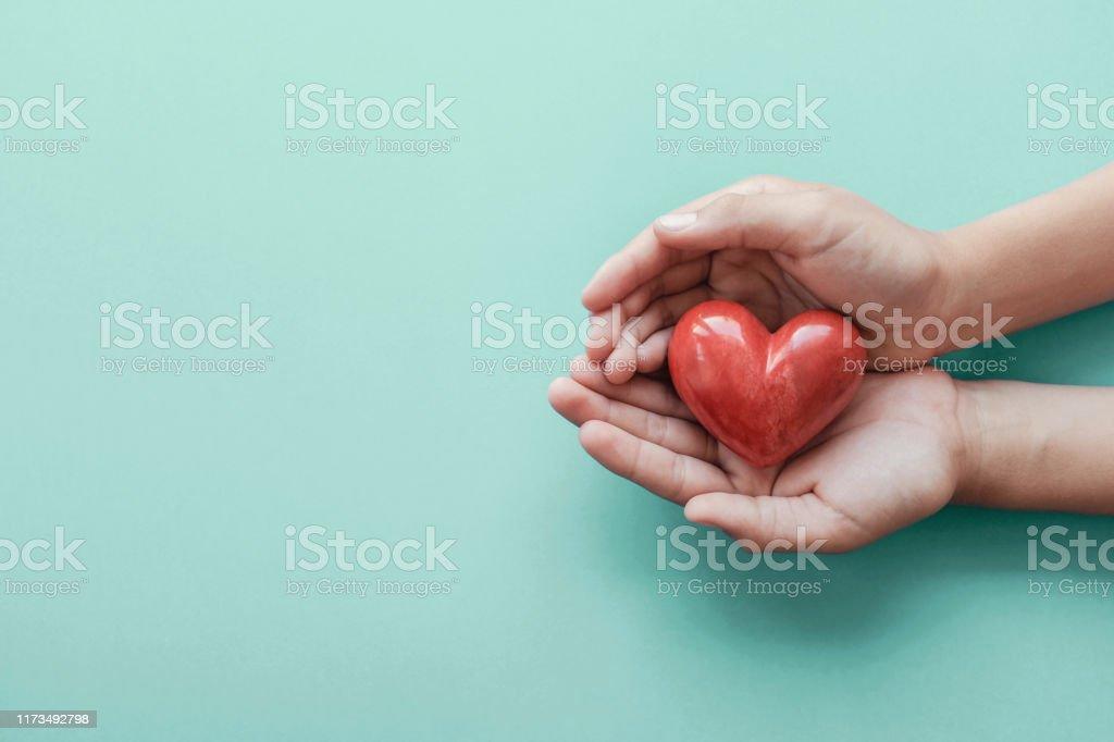 händer som håller rött hjärta på blå bakgrund, hälsovård, kärlek, organdonation, familjeförsäkring och CSR-koncept, World Heart Day, Världshälsodagen - Royaltyfri Adoption Bildbanksbilder