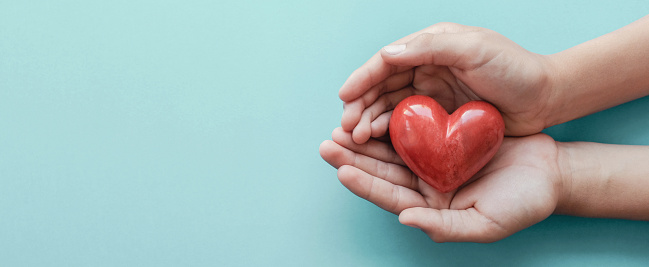 istock hands holding red heart on blue background, health care, love, organ donation, family insurance and CSR concept, world heart day, world health day 1173493820