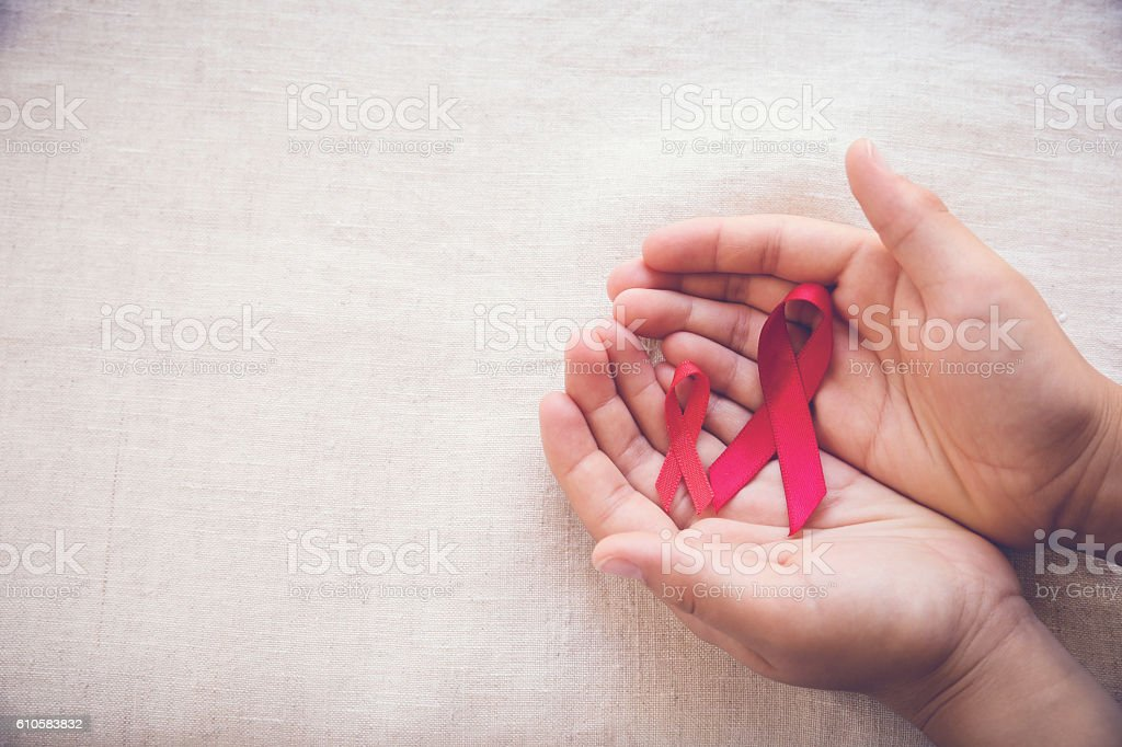 hands holding Red Ribbons on toning background, HIV/AIDS, Anosmi stock photo