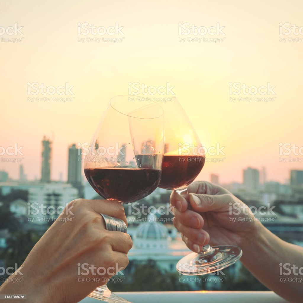 Close up on hands holding red wine glasses on balcony during sunset,...