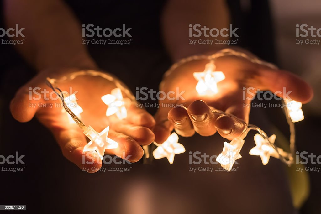 Hands holding shiny Christmas lights with star shapes stock photo