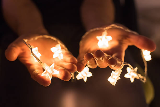hands holding shiny christmas lights with star shapes - gute geschenkideen stock-fotos und bilder